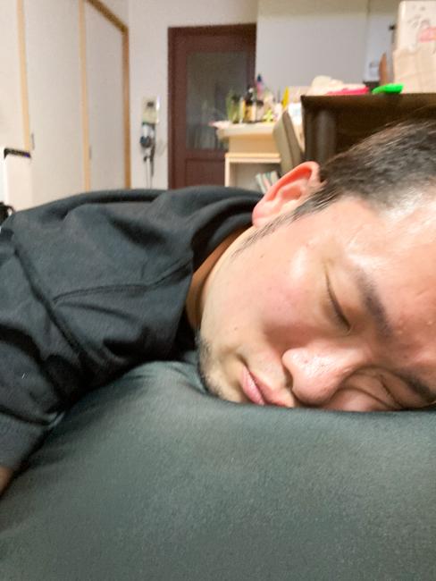 酔っ払った男性がリビングで寝ている画像